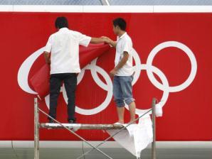 E trabalhadores retiram desenho de anéis olímpicos de fachada em Pequim para colocar o símbolo da...